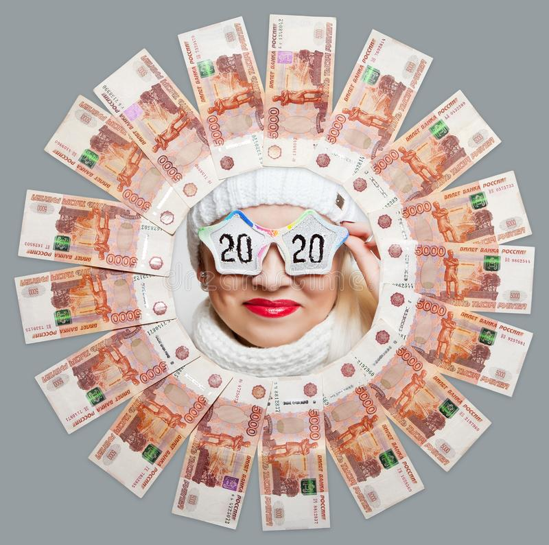 Portrait of a cheerful girl in glasses with the inscription 2020 in the center of the circle of five thousand bills. royalty free stock photo