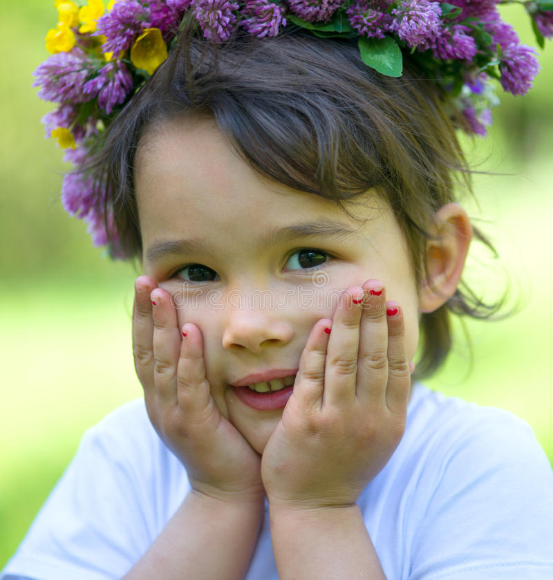 Cheerful little girl with a wreath of flowers on her head royalty free stock images
