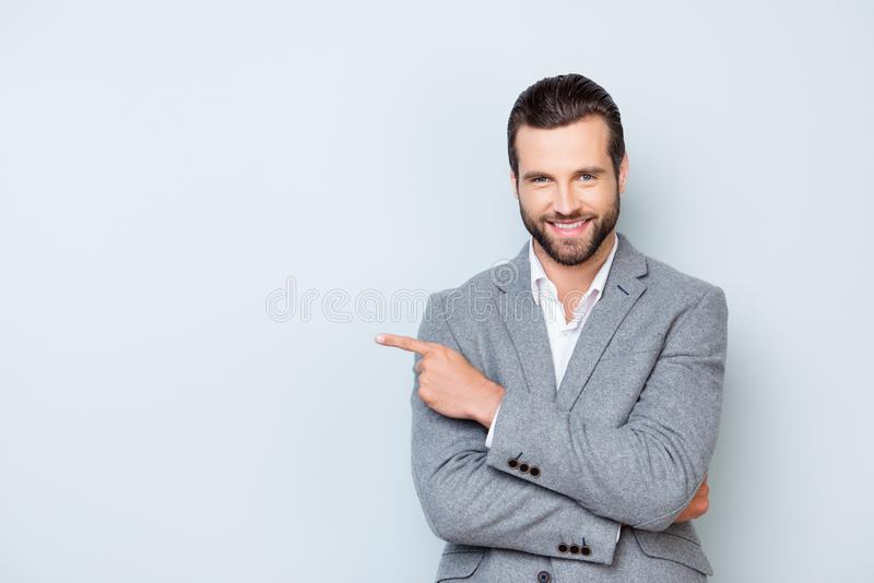 Portrait of cheerful glad man in formal suit standing against g. Ray background and pointing on copyspace stock image