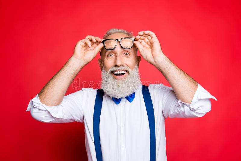 Portrait of cheerful, glad, old man raise his glasses on face, h. Olding eyelet of spectacles with two hands, with wondered expression, open mouth, wearing blue royalty free stock image