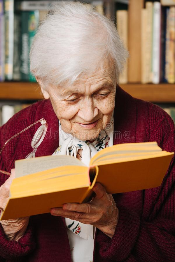 Portrait of cheerful grey haired woman reading book near bookshelf at home royalty free stock photos