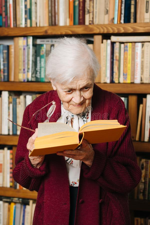 Portrait of cheerful grey haired woman reading book near bookshelf at home stock photos