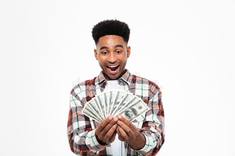 Portrait of a cheerful happy african man. Holding bunch of money banknotes isolated over white background royalty free stock images