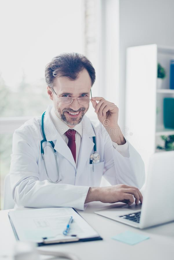 Portrait of cheerful happy doctor in glasses sitting at the desk stock photo