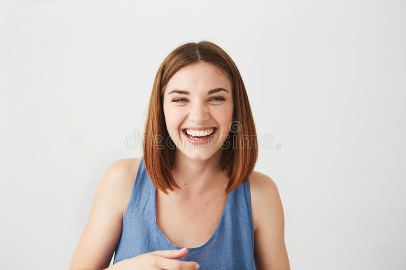 Portrait of cheerful happy young beautiful girl laughing smiling over white background. royalty free stock photography