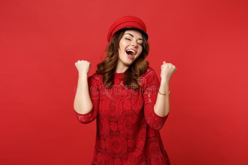 Portrait of cheerful happy young woman in lace dress, cap clenching fists like winner isolated on bright red wall royalty free stock images