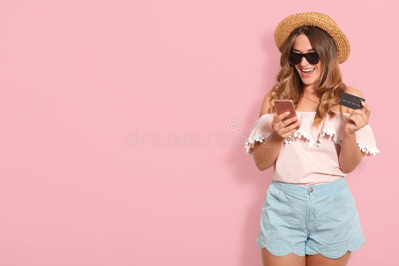 Portrait of cheerful happy young woman wearing summer light pink blouse, blue shorts, black eyeglasses and straw hat holding. Plastic credit card while using royalty free stock image