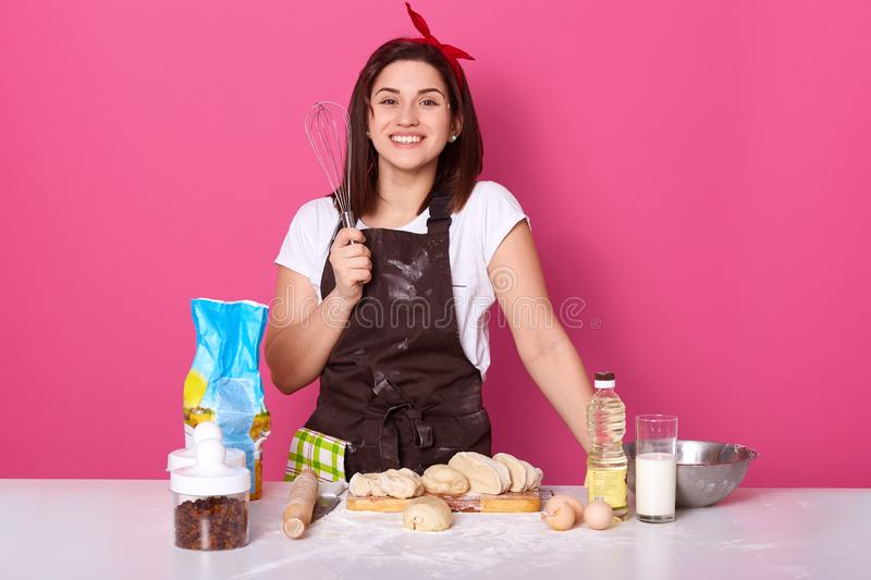 Portrait of cheerful hard working housewife smiling sincerely, holding whisk in one hand, making pastry, standing isolated over. Pink background in studio stock photos
