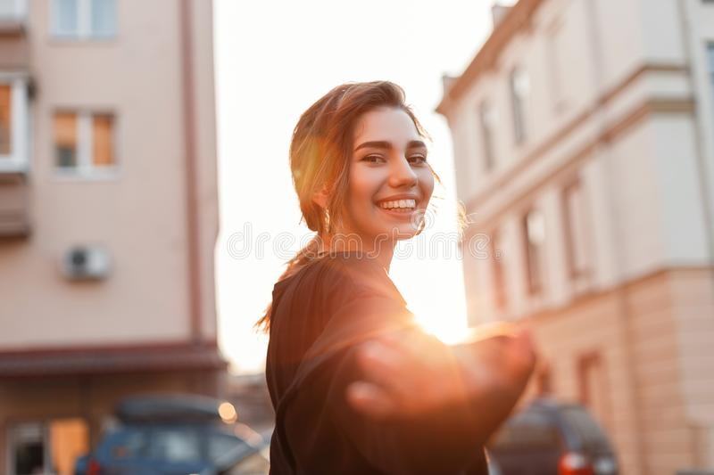 Portrait of a cheerful joyful beautiful young woman with a cute smile in fashionable black clothes outdoors in the city. On a bright sunny day. Positive funny stock images