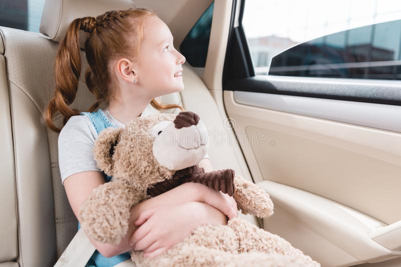 portrait of cheerful kid hugging teddy bear and looking out car window while sitting stock photo