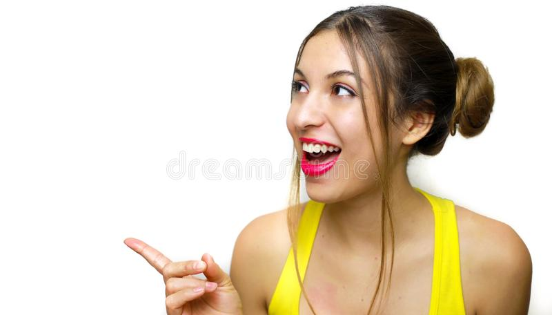 Portrait of cheerful laughing girl with two chingnon pointing by finger at side. Beautiful woman in yellow tank top surprised stock photography