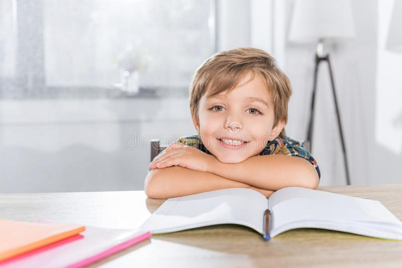 portrait of cheerful little boy sitting at table and looking at camera while stock images