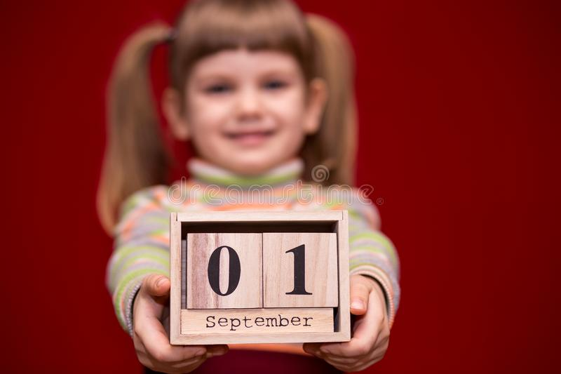 Portrait of cheerful little girl isolated on red hold wooden calendar set on first september. Focus on calendar. Back to school stock photos