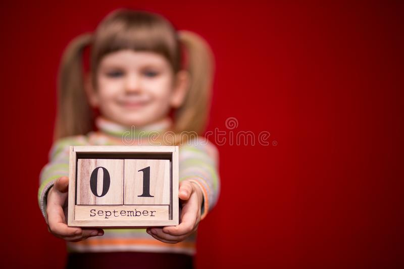 Portrait of cheerful little girl isolated on red hold wooden calendar set on first september, focus on calendar. Back to school royalty free stock photos