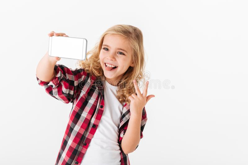Portrait of a cheerful little girl taking a selfie. Over white background stock photo