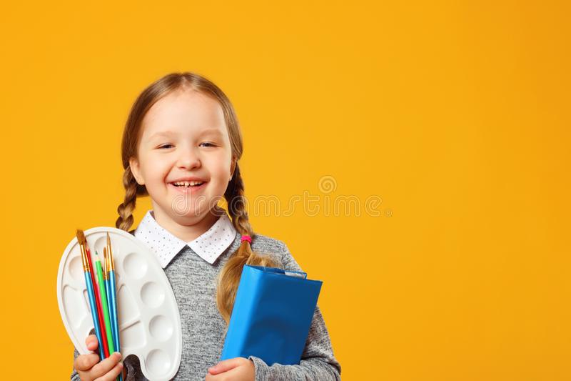 Portrait of a cheerful little girl on a yellow background. Schoolgirl holds a book, pencils, brushes and a palette. stock photos