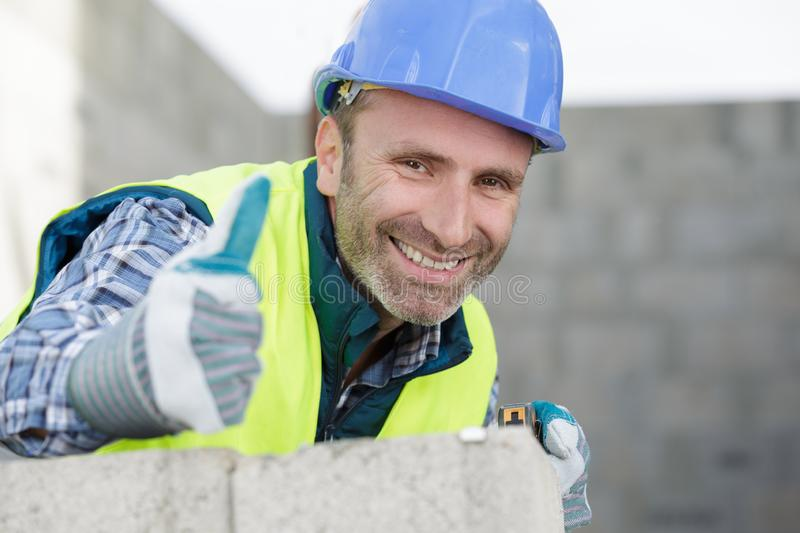 Portrait cheerful male builder showing thumbs up. Portrait of a cheerful male builder showing thumbs up stock image