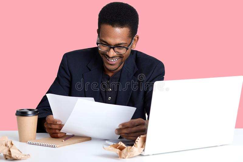 Portrait of cheerful male financier with dark skin, wears glasses, has fan expression, prepares report, drinks coffee, laughing stock image