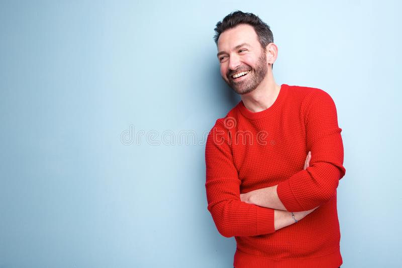 Cheerful man with beard laughing against blue background. Portrait of cheerful man with beard laughing against blue background royalty free stock photography
