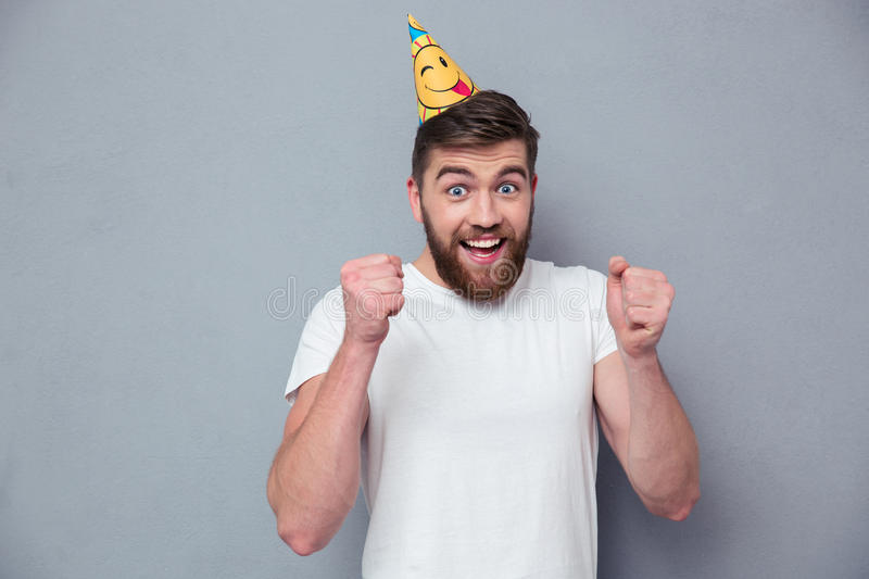 Portrait of a cheerful man with birthday hat. Standing over gray background royalty free stock photos