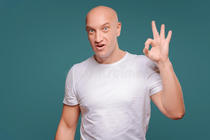 Portrait of a cheerful man showing okay gesture isolated on the blue background stock photos