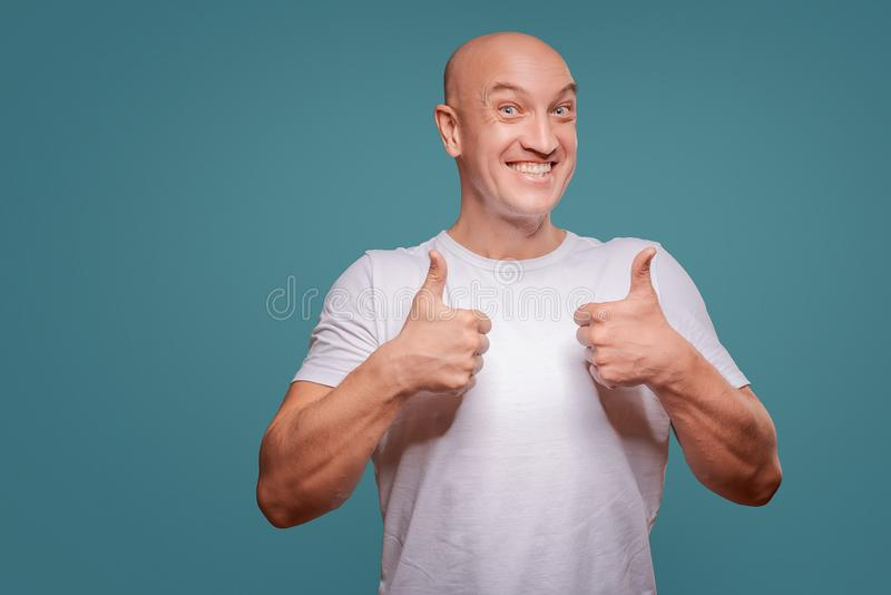 Portrait of a cheerful man showing okay gesture isolated on the blue background royalty free stock photos