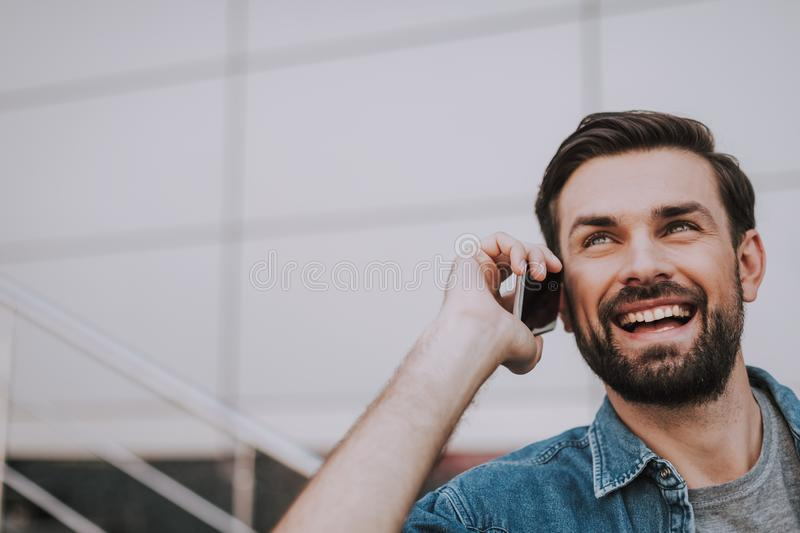 Positive male talking on mobile at street stock photography