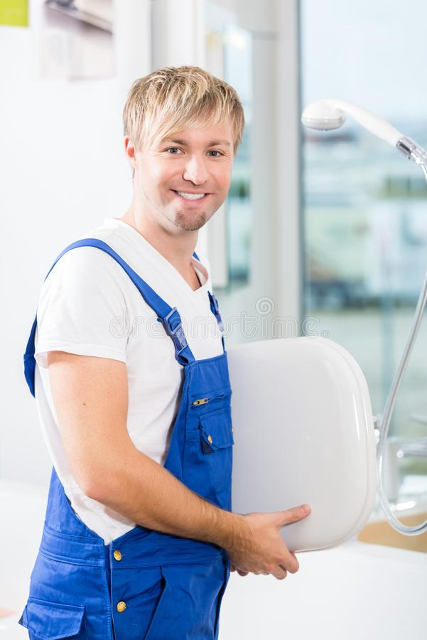 Portrait of a cheerful man working in a sanitary ware shop. Portrait of a cheerful man wearing blue overall while working in a sanitary ware shop with modern stock photography