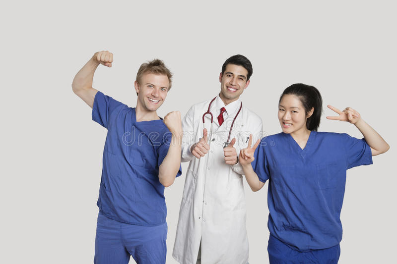Download Portrait Of A Cheerful Medical Team Gesturing Over Gray Background Stock Image - Image of diversity, male: 29672325