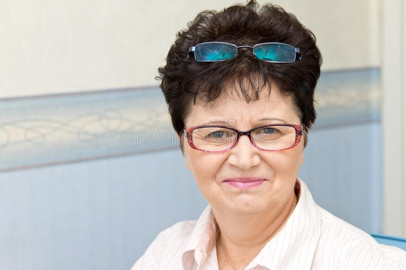 Portrait of cheerful middle-aged woman holding two pairs of glasses royalty free stock image