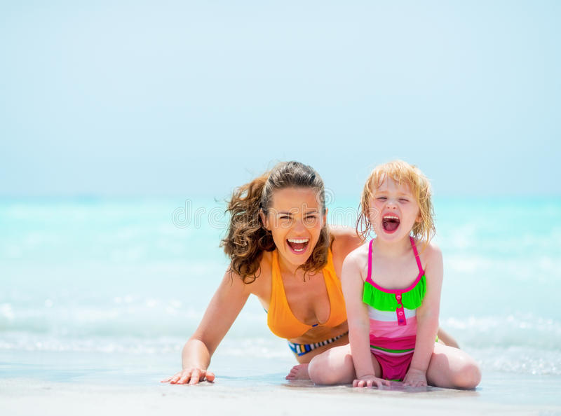 Portrait of cheerful mother and baby girl on beach. Portrait of cheerful mother and baby girl on sea shore stock photos