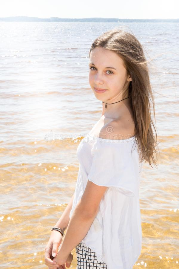 Cheerful natural young girl with long hair on water sand sea beach. Portrait of cheerful natural young girl with long hair on water sand sea beach royalty free stock photography