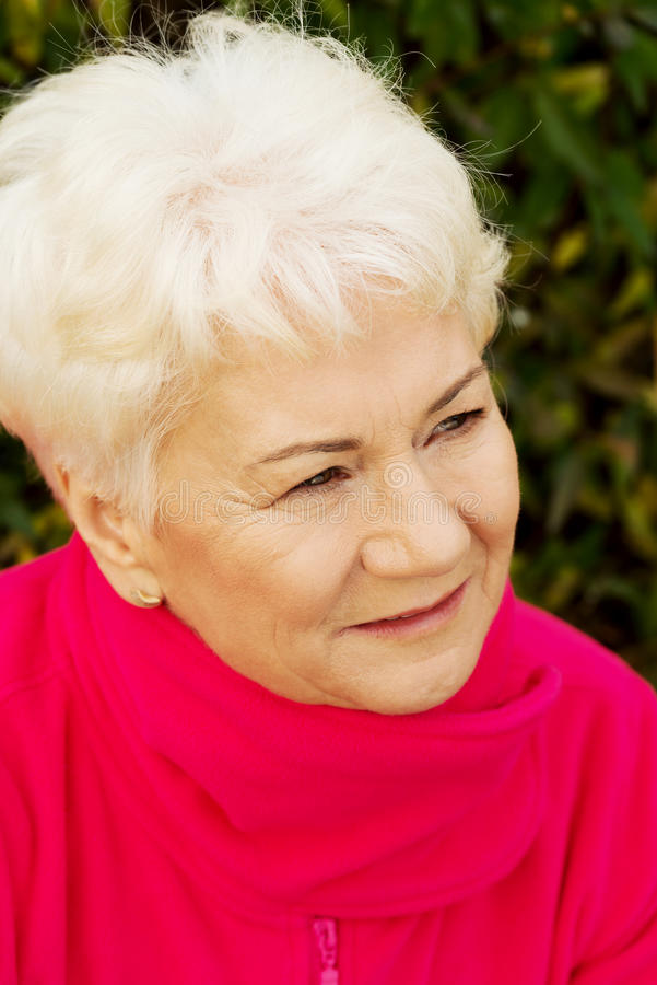 Portrait of a cheerful old lady over green background. stock images