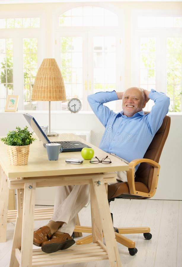 Portrait of cheerful old man in his study royalty free stock photos