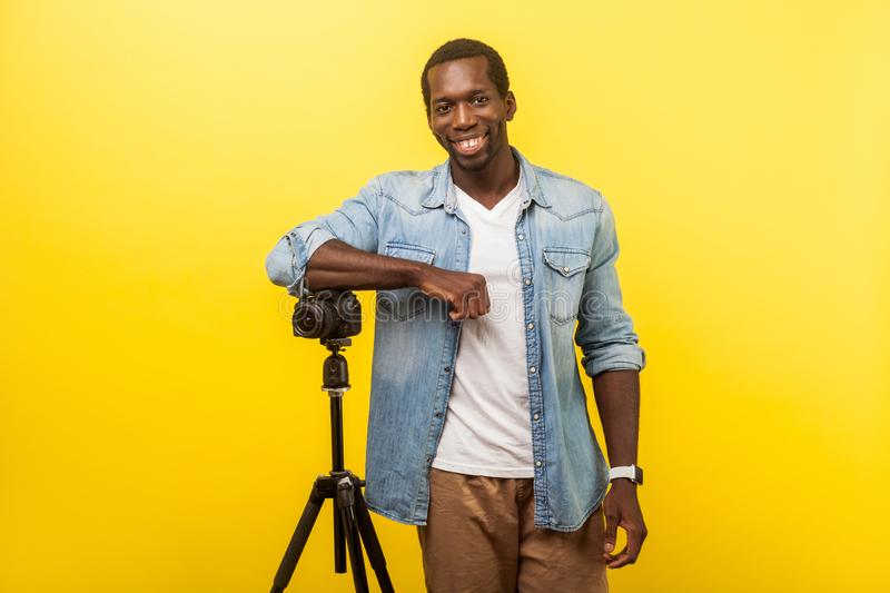 Portrait of cheerful photographer or traveler with professional digital dslr camera on tripod. indoor studio shot isolated on. Portrait of cheerful photographer royalty free stock photography