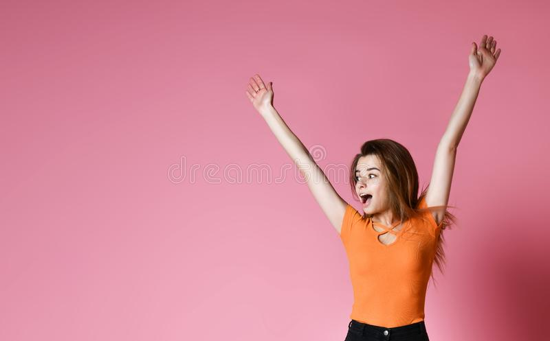 Portrait of cheerful positive girl jumping in the air looking away camera isolated on pink background. stock photo