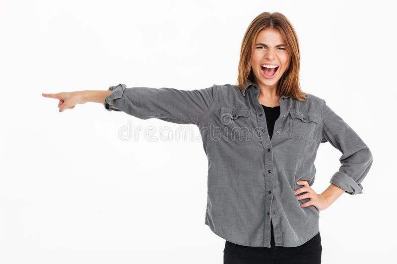 Portrait of a cheerful pretty girl pointing finger away stock photo