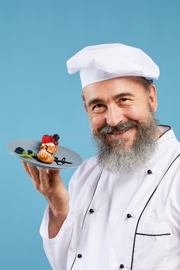 Smiling Senior Chef Holding Dessert on Blue stock photos