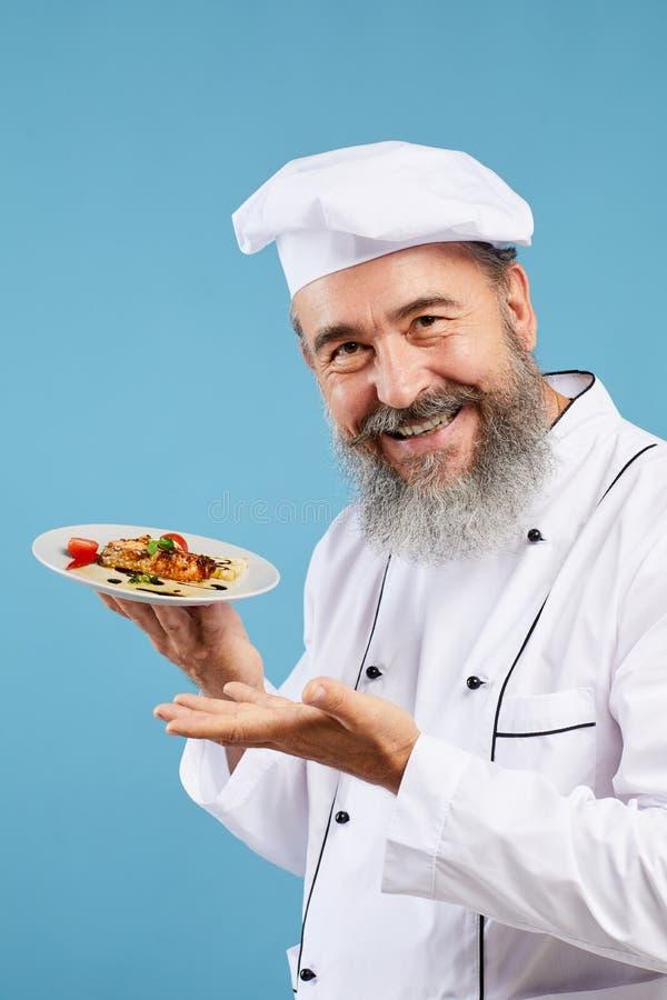 Smiling Senior Chef Presenting Dish on Blue stock photos