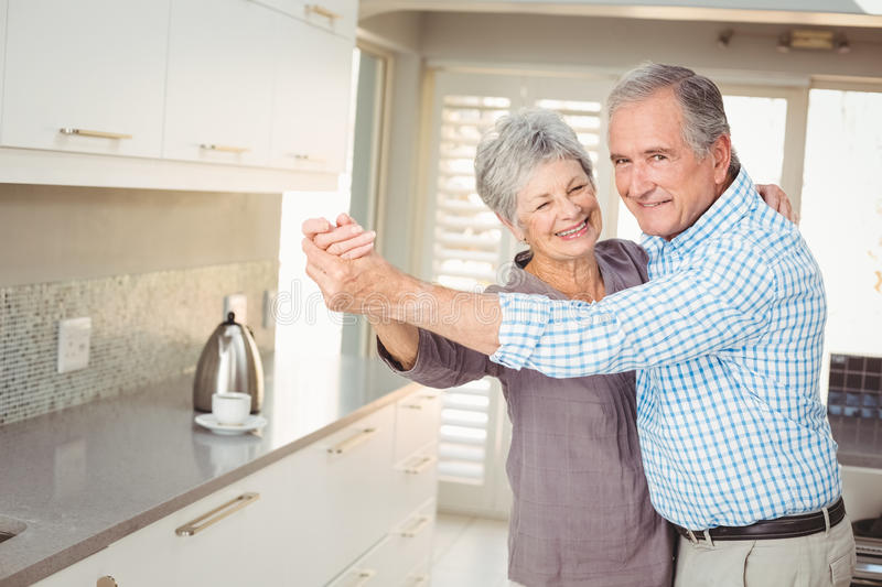Portrait of cheerful senior man dancing with wife stock photo