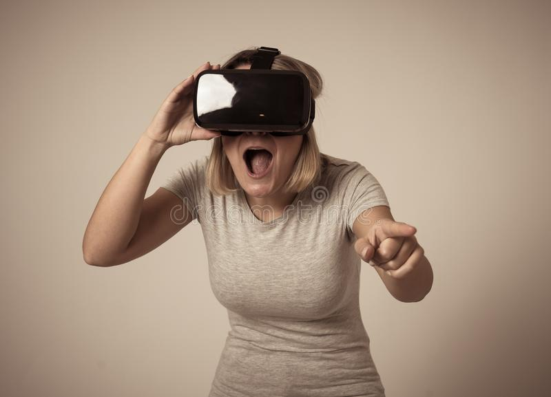 Portrait of cheerful and shocked young woman wearing Virtual Reality headset exploring 3D world. Amazed woman getting experience using VR headset glasses royalty free stock photo