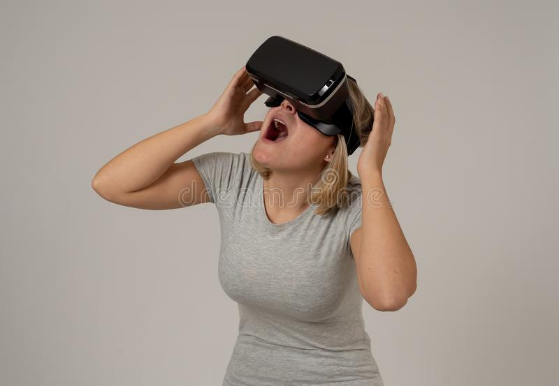 Portrait of cheerful and shocked young woman wearing Virtual Reality headset exploring 3D world. Amazed woman getting experience using VR headset glasses royalty free stock images