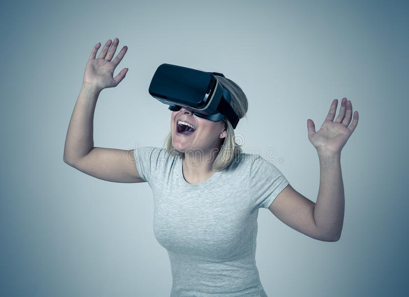 Portrait of cheerful and shocked young woman wearing Virtual Reality headset exploring 3D world. Amazed woman getting experience using VR headset glasses stock photography