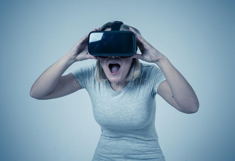 Portrait of cheerful and shocked young woman wearing Virtual Reality headset exploring 3D world. Amazed woman getting experience using VR headset glasses stock photo