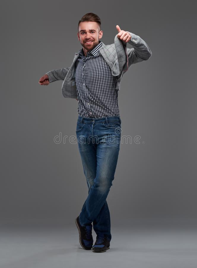 Portrait of cheerful smiling man in checkered shirt, denim and blazer on his shouder. He looks very happy royalty free stock image