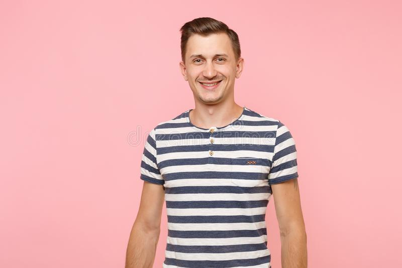 Portrait of cheerful smiling young hipster man dresssed casually in striped t-shirt isolated on trending pink background royalty free stock photography