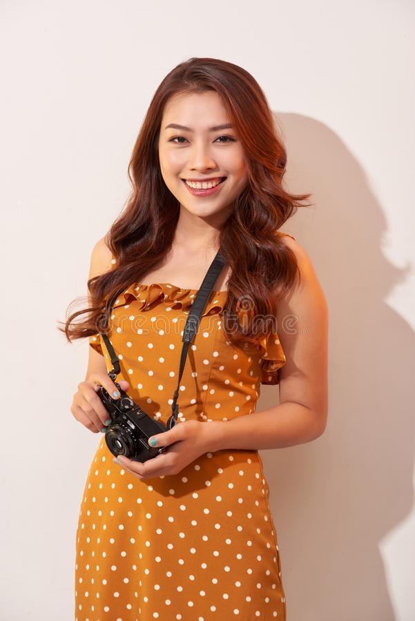 Portrait of cheerful smiling young woman taking photo with inspiration and wearing summer dress. Girl holding retro camera. Model stock photos