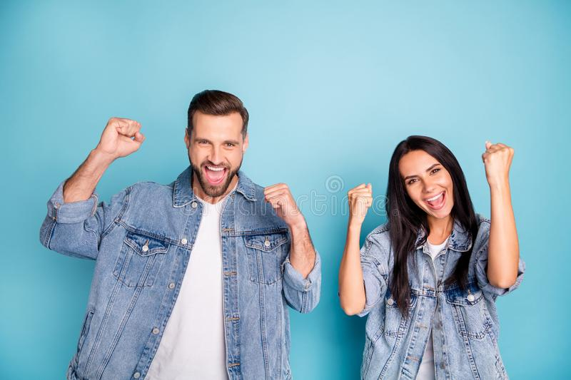 Portrait of cheerful spouses raising fists screaming yeah wearing denim jeans isolated over blue background. Portrait of cheerful spouses raising, fists royalty free stock photo