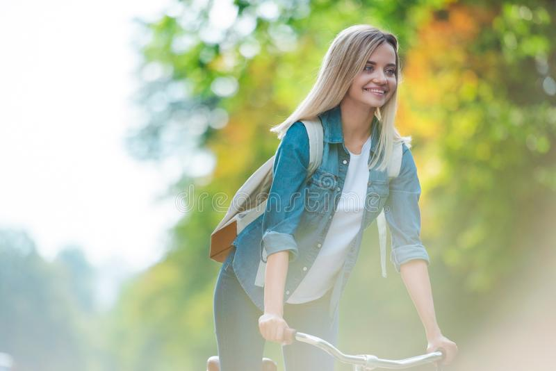 portrait of cheerful student with backpack riding bicycle stock photography