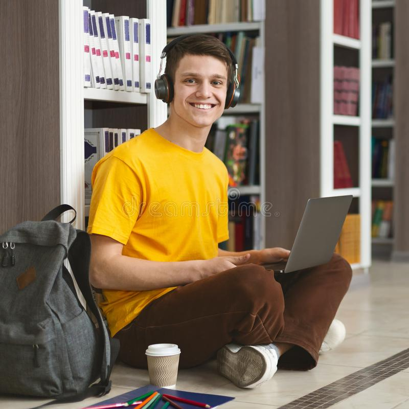 Portrait of cheerful student working on new project at library. Creative caucasian guy sitting on the floor at library, working on new project and using laptop royalty free stock image